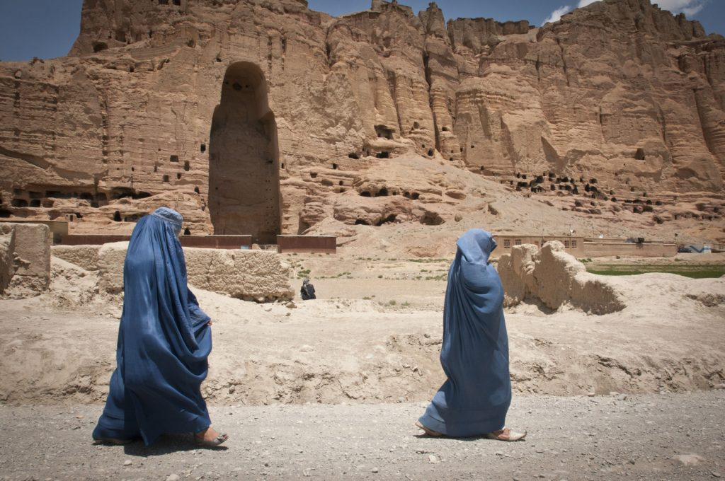 "Two women walk past the huge cavity where one of the ancient Buddhas of Bamiyan, known to locals as the ""Father Buddha,"" used to stand, June 17, 2012. The monumental statues were built in A.D. 507 and 554 and were the largest statues of standing Buddha on Earth until the Taliban dynamited them in 2001."